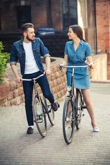 Pareja joven sentado en bicicleta frente a la ciudad