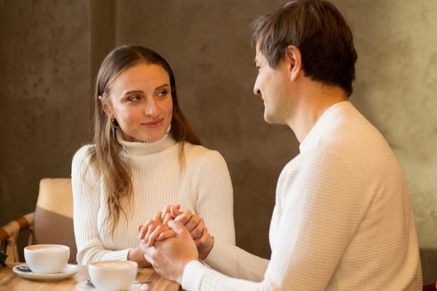Pareja joven, sentado, en, caffe, con, café, y, mirar el uno al otro