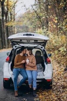 Pareja joven sentado en la parte trasera de un coche bebiendo té en el bosque