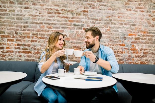 Pareja joven sentado en el sofá a la mesa en el vestíbulo del hotel a su llegada, bebiendo café juntos, sonriendo felices.