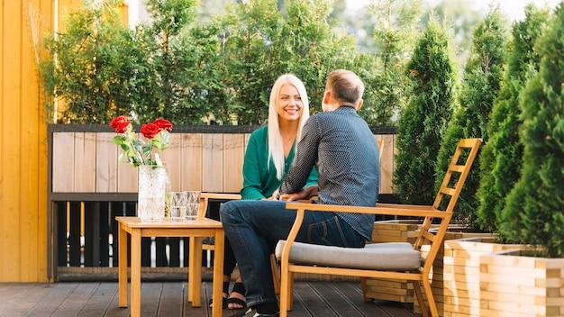 Pareja joven sentado en la terraza del patio