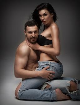 Pareja joven sexy hermosa pareja sexy en el amor sobre fondo gris vestida con pantalones de mezclilla.