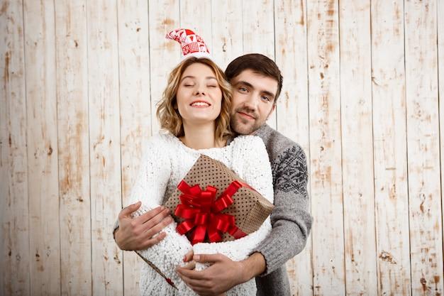 Pareja joven sonriendo abrazando la celebración de regalo de navidad sobre pared de madera