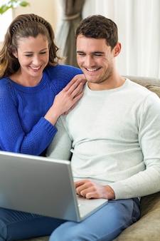 Pareja joven sonriendo cara a cara en el sofá y usando una computadora portátil en la sala de estar