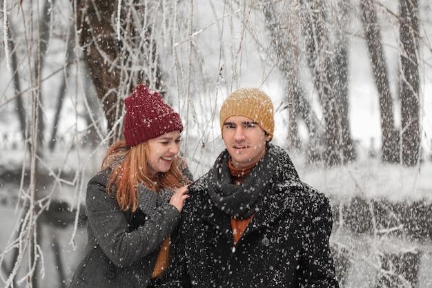 Pareja joven sonriendo y jugando con la nieve
