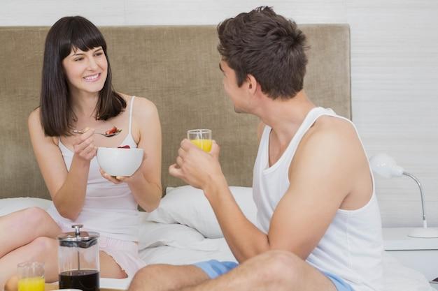 Pareja joven sonriendo mientras desayunando juntos en el dormitorio