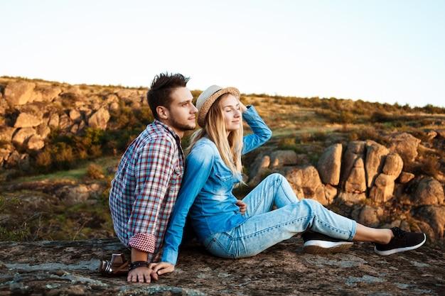 Pareja joven sonriendo, sentado en la roca en el cañón, disfrutando de la vista