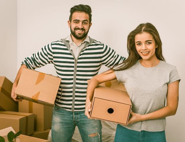 Pareja joven sonriendo y sosteniendo cajas mientras está parado entre cajas desempaquetadas