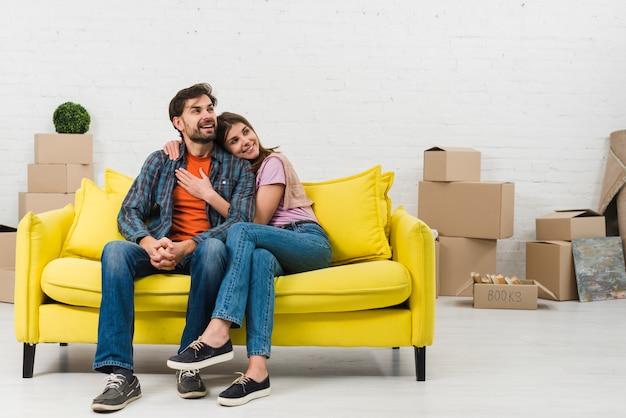 Pareja joven sonriente cariñosa que se sienta en el sofá amarillo en su nueva casa