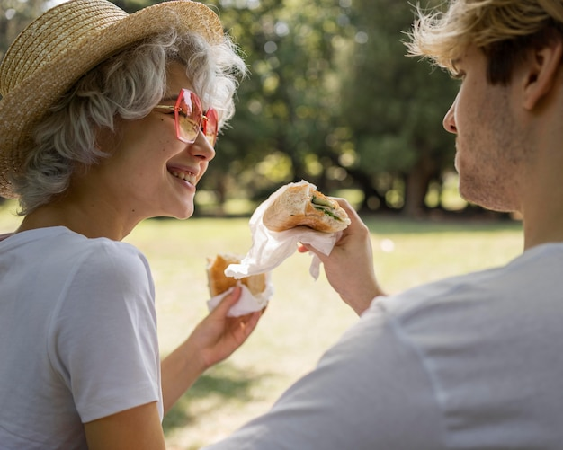 Pareja joven sonriente comiendo hamburguesas juntos en el parque