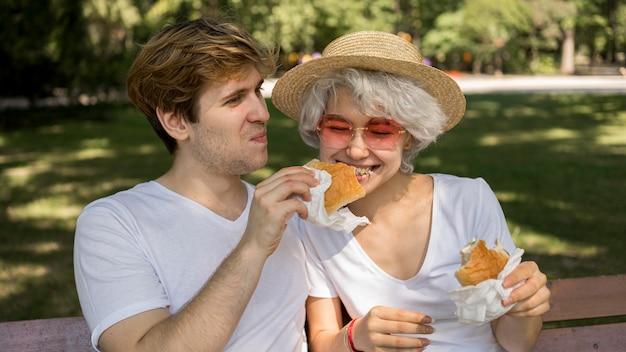 Pareja joven sonriente comiendo hamburguesas en el parque
