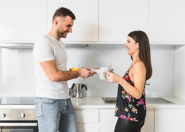 Pareja joven sonriente desayunando en la cocina