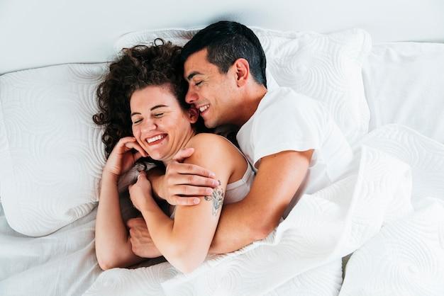 Pareja joven sonriente bajo edredón en cama