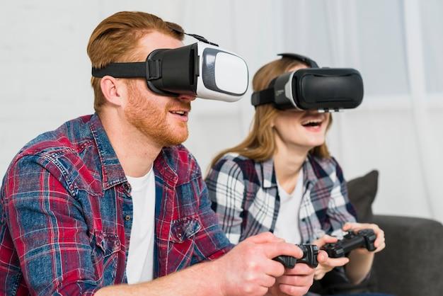 Pareja joven sonriente con gafas de realidad disfrutando de jugar el videojuego
