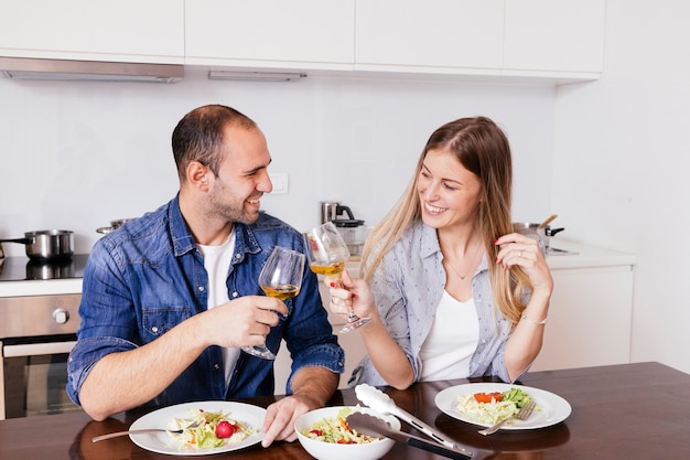 Pareja joven sonriente que come la ensalada que tuesta con las copas de vino en la cocina
