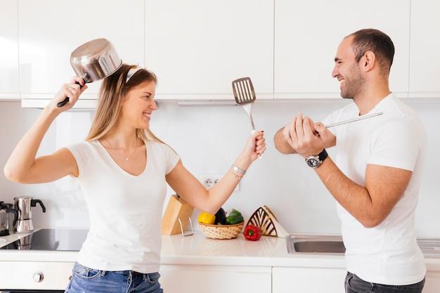 Pareja joven sonriente que lucha con el utensilio y la espátula en la cocina