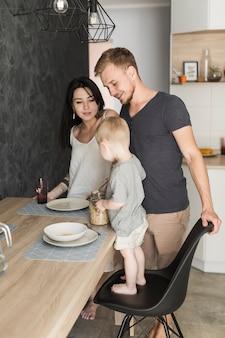 Pareja joven sonriente que mira al niño pequeño que se coloca en silla que sirve avena en la placa en el desayuno
