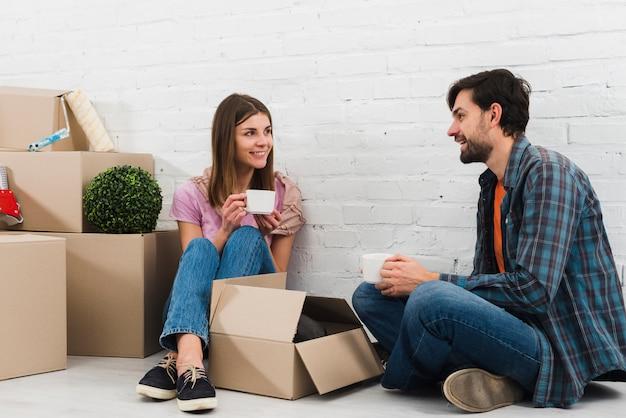Pareja joven sonriente sentada en el piso con cajas de cartón en movimiento tomando el café