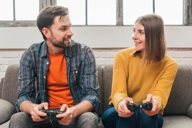 Pareja joven sonriente sentada en el sofá mirando el uno al otro mientras juega videojuegos