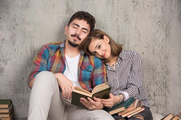 Pareja joven sonriente sentada en el suelo con libros