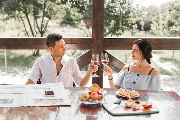 Pareja joven sonriente tostado copas de vino con frutas de manzana en la mesa