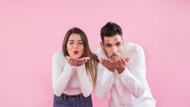 Pareja joven soplando besos sobre fondo rosa