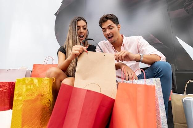 Pareja joven sorprendida mirando dentro de bolsas de compras