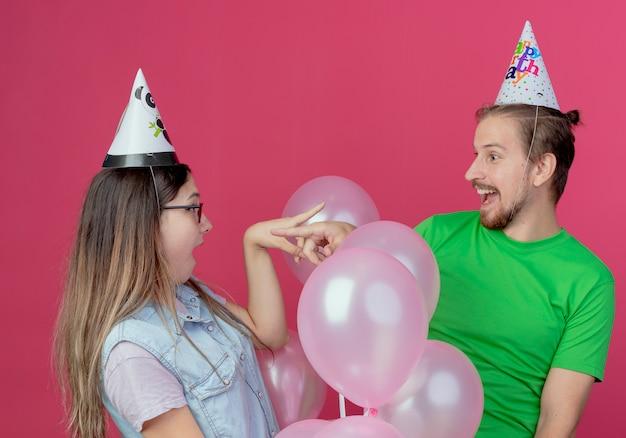 Pareja joven sorprendida con sombrero de fiesta mira y apunta el uno al otro de pie con globos de helio aislados en la pared rosa