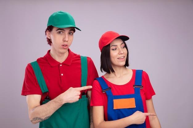 Pareja joven sorprendido chico chica alegre en uniforme de trabajador de la construcción y gorra apuntando al chico de lado mirando a la cámara chica mirando al lado aislado en la pared blanca