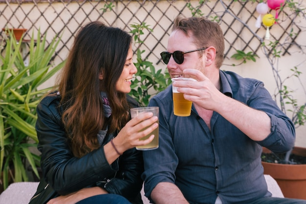 Pareja joven sosteniendo dos tazas de cerveza y vítores. concepto de fiesta de bebidas frías. feliz pareja divirtiéndose mientras bebe cerveza al aire libre. amigos haciendo un brindis. concepto de diversión y ocio.