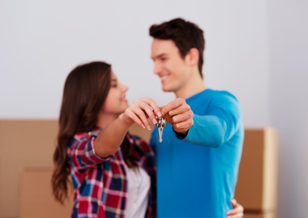 Pareja joven sosteniendo la llave al nuevo hogar en la mano