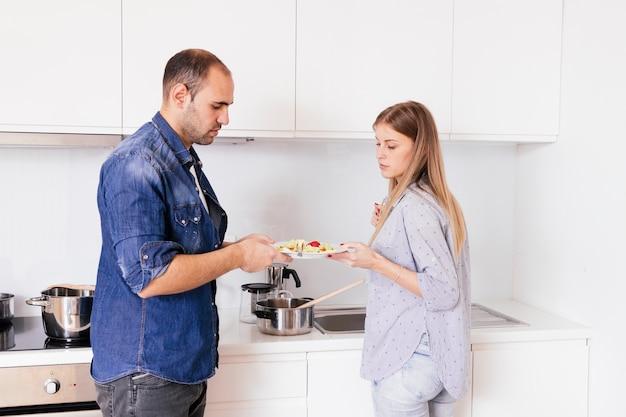 Pareja joven sosteniendo el plato de ensalada en la cocina