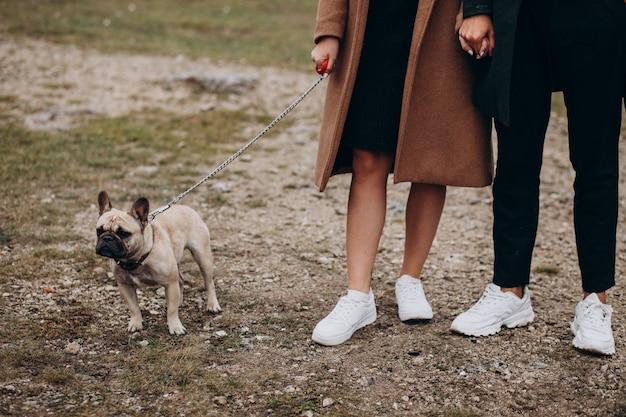Pareja joven con su bulldog francés en el parque