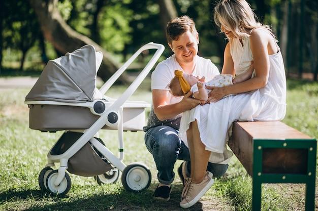 Pareja joven con su pequeña hija en el parque sentado junto a su cochecito de bebé