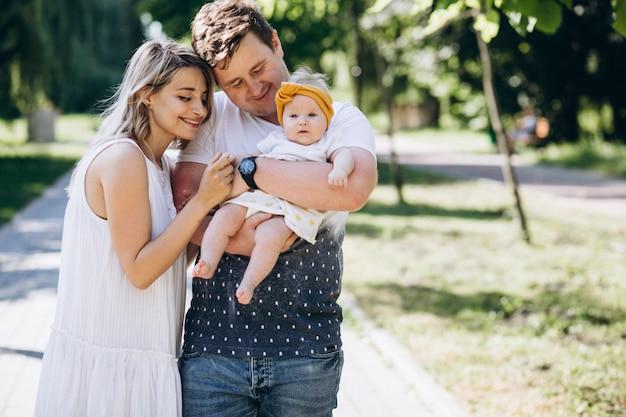 Pareja joven con su pequeña hija en el parque