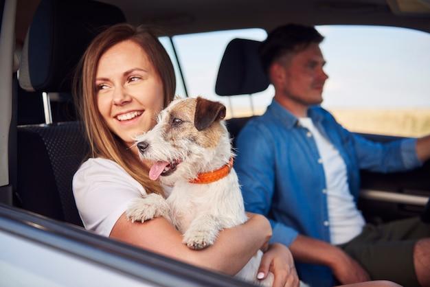 Pareja joven y su perro viajando juntos en un coche