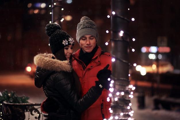 Pareja joven en suéteres y gorras abrazar en la calle de invierno. enamorado en una guirnalda.