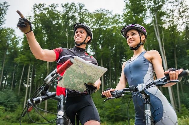 Pareja joven con las suyas bicicletas de pie cerca del bosque.