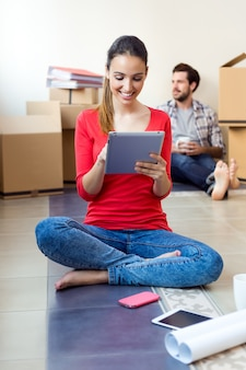 Pareja joven con tableta digital descansando en su nuevo hogar
