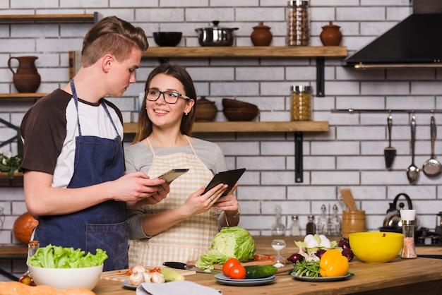 Pareja joven con tabletas digitales cocinando juntos