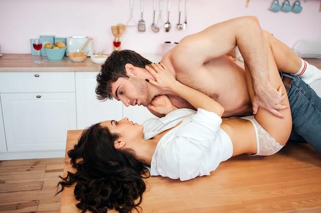 Pareja joven teniendo sexo en la cocina. guy se para encima de ella.