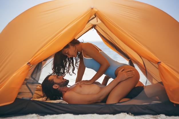 Pareja joven teniendo sexo en una tienda de campaña en la naturaleza pareja íntima disfrutando de las relaciones sexuales en el