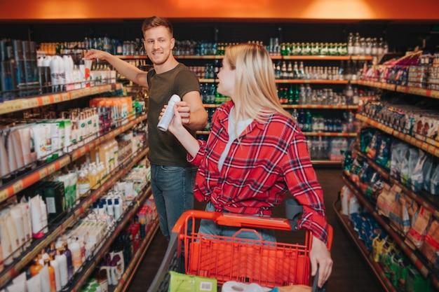 Pareja joven en la tienda de comestibles. la mujer recibe desodorante del hombre. se quedó mirando los estantes de higiene. la gente se mira a cada uno y sonríe. compradores alegres.