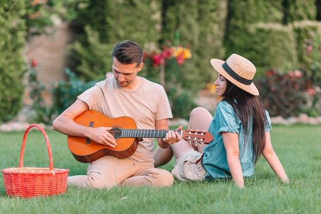 Pareja joven tocando la guitarra en el césped