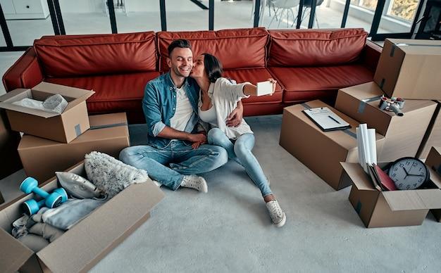 Pareja joven tomando autorretratos con su teléfono inteligente en su nuevo hogar. mudanza, compra de una casa, concepto de apartamento.