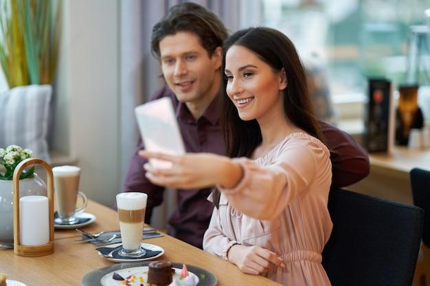 Pareja joven tomando selfie en cafe