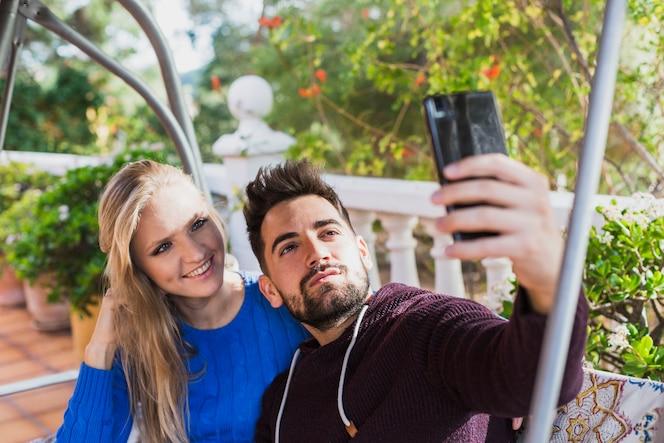 Pareja joven tomando selfie en la terraza