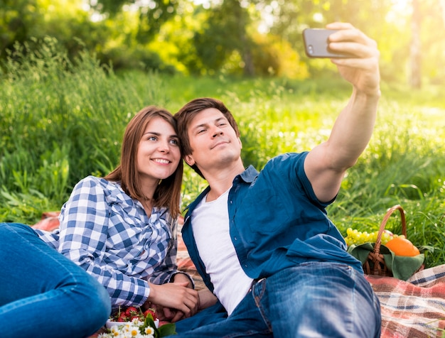 Pareja joven tomando selfie en plaid fuera