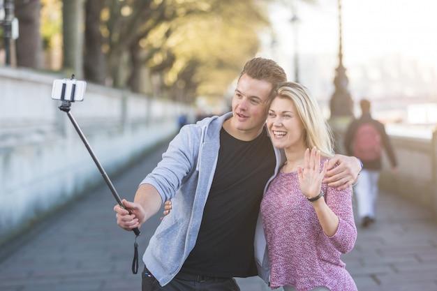 Pareja joven tomando un selfie con smartphone en el palo