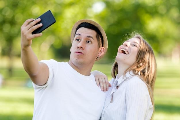 Pareja joven tomando un selfie en su móvil en el parque. hombre latino y mujer caucásica